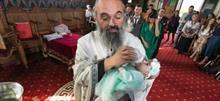 Παπάς ταΐζει μωράκι στην βάφτιση για να το ηρεμήσει
